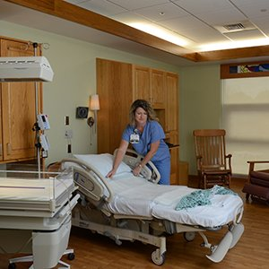 Nurse adjusting bed in a birthing suite