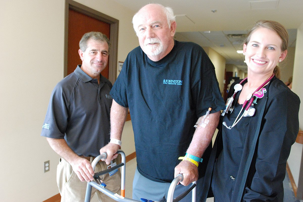 Henry Butts walks down the hall at Johnston Health after his knee replacement.